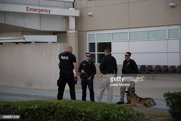 Police officers guard the emergency entrance at Arrowhead Regional Medical Center where numerous victims of a mass shooting at the Inland Regional...