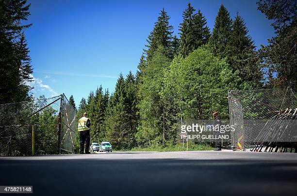 Police officers guard the gate of the perimeter fence that surrounds Elmau castle on June 4, 2015 in Klais near Kruen, southern Germany. Germany will...