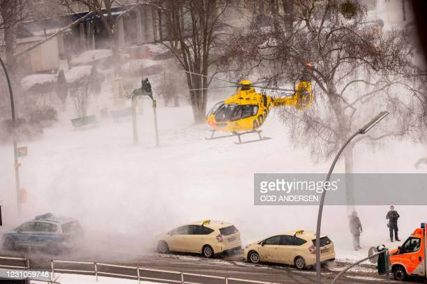 Police officers guarding the perimeter get covered in snow as an ADAC medical rescue helicopter takes off from Bayerischer Platz in Berlin's...