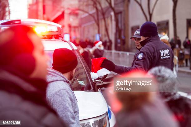 Police officers hang a Santa hat an NYPD vehicle at Rockefeller Center on Christmas day on December 25 2017 in New York City Security in New York is...