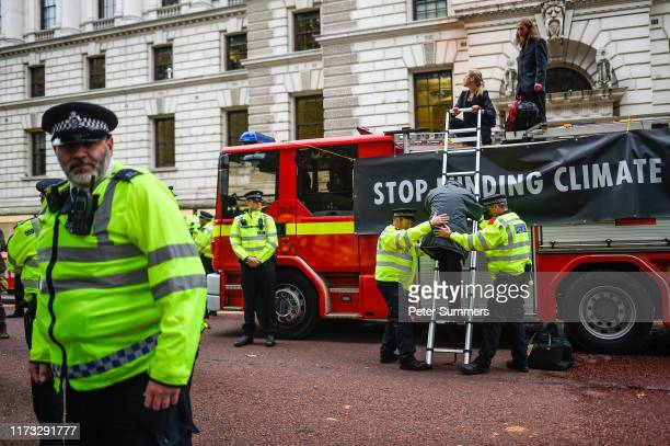 Police officers help a climate change activist down from a fire truck outside the Treasury building on October 3 2019 in London England Climate...