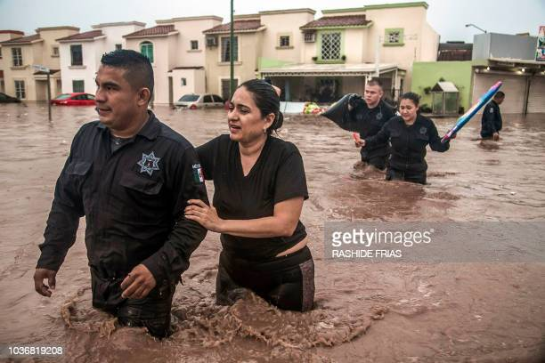 TOPSHOT Police officers help a woman cross a flooded street in Culiacan Sinaloa State Mexico on September 20 2018 Heavy rains have flooded different...