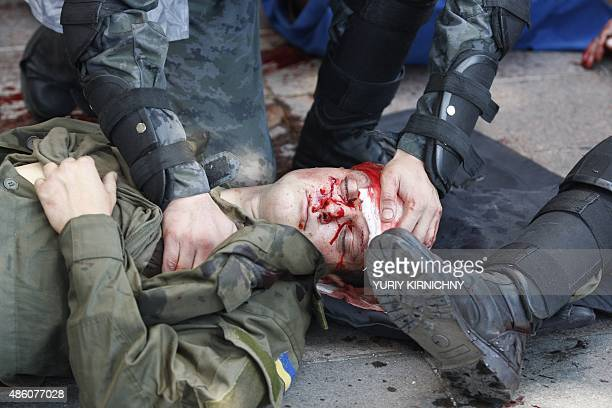 Police officers help a wounded colleague during clashes with activists of few radical Ukrainian parties in front of the parliament in Kiev on August...