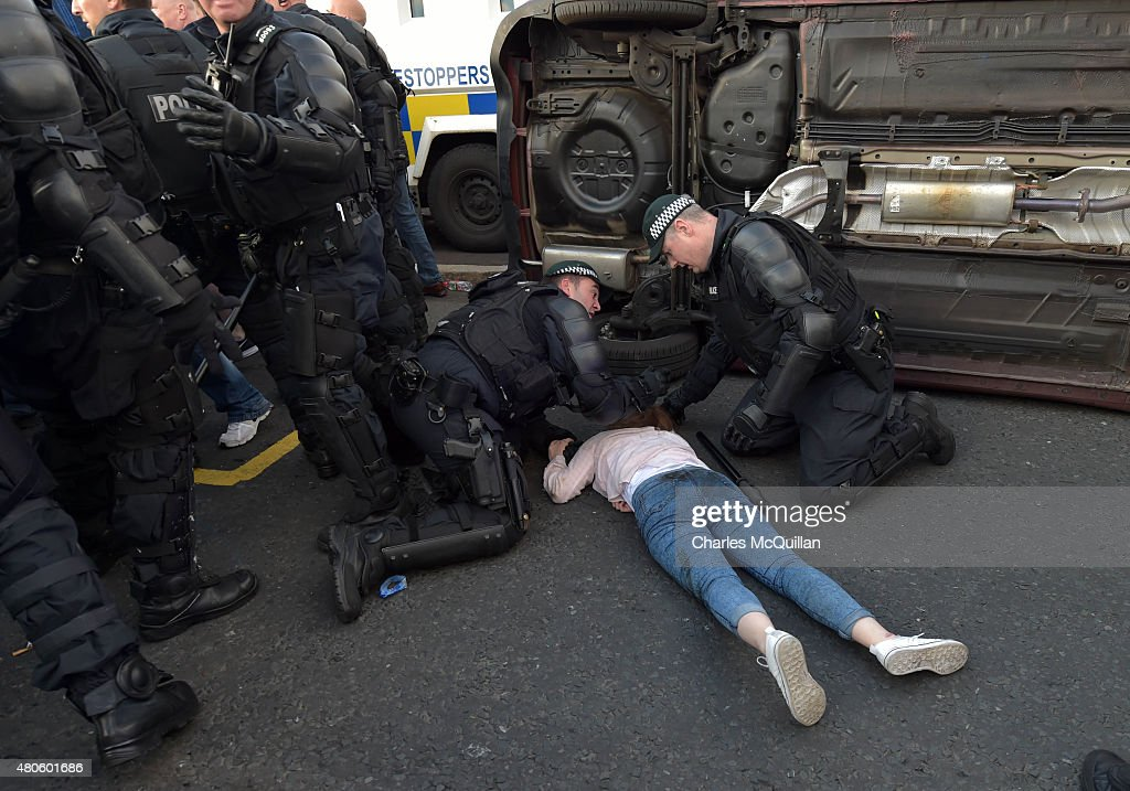 Police officers help Phoebe Clawson, 16, who was trapped underneath a moving car after an alleged loyalist drove over her as they reversed at high speed on the return journey towards the controversial Ardoyne flashpoint during the Twelfth of July parade on July 13, 2015 in Belfast, Northern Ireland. Phoebe Clawson suffered a broken collarbone, broken ankle and shattered pelvis following the incident. John Aughey, 61, was arrested following the incident and has been charged with two counts of attempted murder. Mr. Aughey has been prominent in the ongoing loyalist protest at the Twaddell Avenue/Ardoyne interface and has acted as a spokesman for Orange lodges caught up in the dispute. The Twelfth is an Ulster Protestant celebration held annually. It celebrates the victory of Protestant king William of Orange over Catholic king James II at the Battle of the Boyne in 1690, which helped ensure Protestant supremacy in Ireland at that time. This year the Twelfth takes place on the thirteenth of July due to the original date falling on a Sunday.