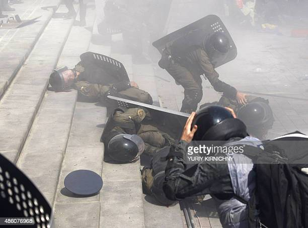 Police officers help wounded colleagues during clashes with activists of few radical Ukrainian parties in front of the parliament in Kiev on August...