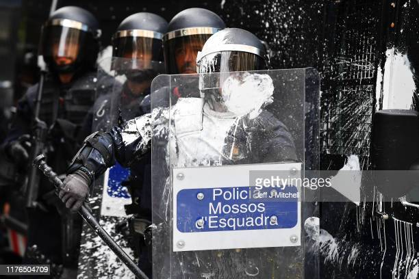 Police officers hit by a white substance as they observe demonstrators gathering following a week of protests over the jail sentences given to...