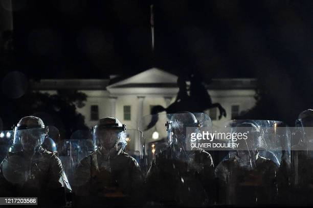 Police officers hold a perimeter behind the metal fence recently erected in front of the White House demonstrators gather to protest the killing of...