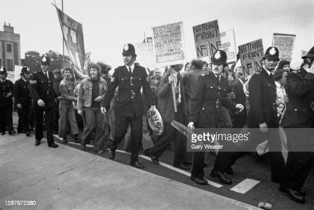 Police officers holding dustbin lids seen escorting a National Front march in New Cross, London, England, 12th August 1977. The dustbin lids are...