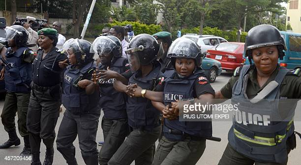 Police officers holds arms to block supporters of 219 schoolgirls kidnapped by Boko Haram militants from marching on the president's official...
