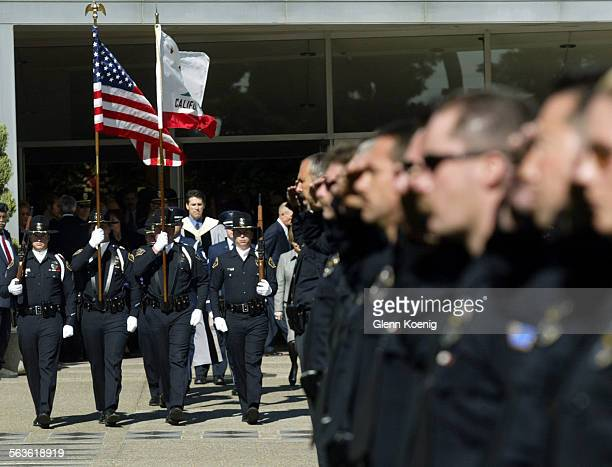 Police officers in a line of honor, salute family and friends as they exit the Crystal Cathedral in Garden Grove after services for Police officer...