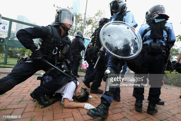 Police officers in antiriot gear holds down an antiextradition bill protestor near the Legislative Council Complex on June 12 2019 in Tamar Hong Kong...