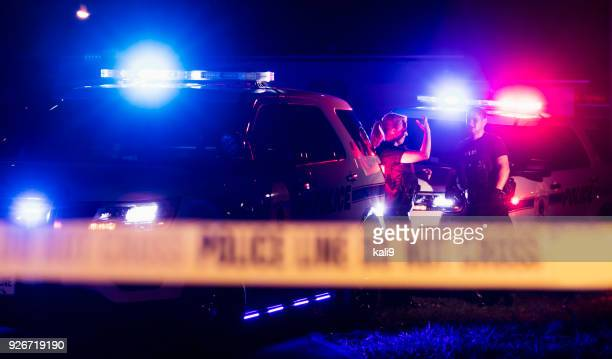 police officers in bulletproof vests behind cordon tape - cordon tape stock pictures, royalty-free photos & images