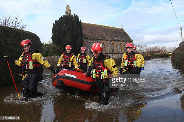 Police officers in drysuits use a boat to patrol the flooded and largely evacuated village of Moorland on the Somerset Levels on February 19 2014 in...