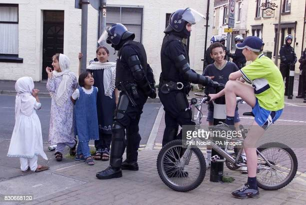 Police officers in full riot gear talk to white and asian children as they try to maintain calm on the street's of Burnley Lancashire after a weekend...