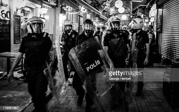 CONTENT] Police officers in full riot gear walk down a side street off Istiklal street looking for protestors after a large protest during the day...