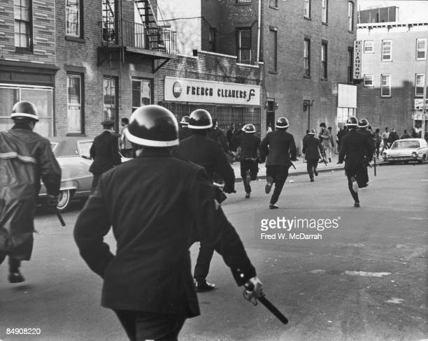 Police officers in helmets and with drawn batons run across Howard Avenue in pursuit of bottlethrowing students during a school strike Brooklyn New...