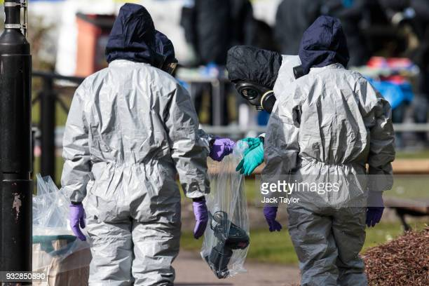 Police officers in protective suits and masks bag up a camera they used in investigations at the scene where former doubleagent Sergei Skripal and...