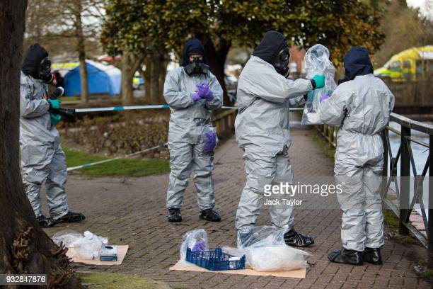 Police officers in protective suits and masks collect samples near the scene where former doubleagent Sergei Skripal and his daughter Yulia were...