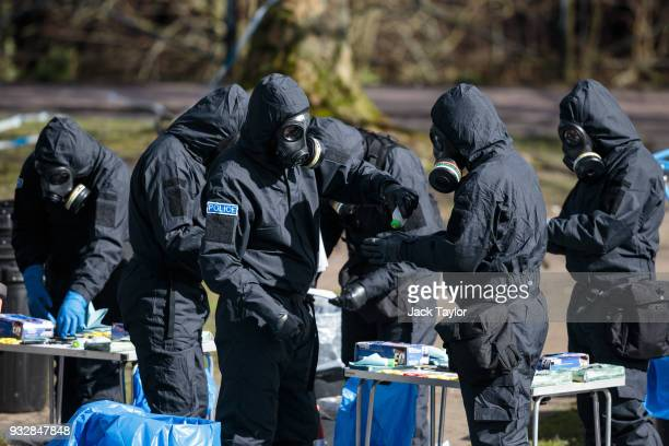 Police officers in protective suits and masks work near the scene where former doubleagent Sergei Skripal and his daughter Yulia were discovered...