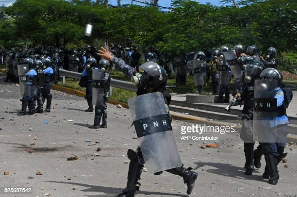 Police officers in riot gear clash with students from the National Autonomous University of Honduras gathered under the University Student Movement...