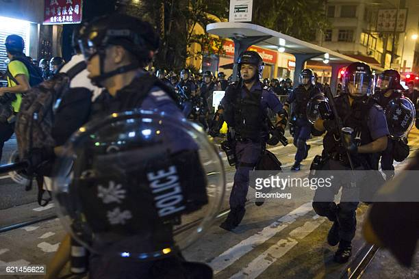 Police officers in riot gear disperse demonstrators not pictured during a protest near the Liaison Office of the Central People's Government in Hong...