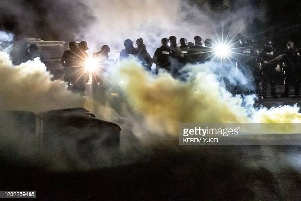 Police officers in riot gear fire tear gas in front of the Brooklyn Center Police Station as people gather to protest after a police officer shot and...