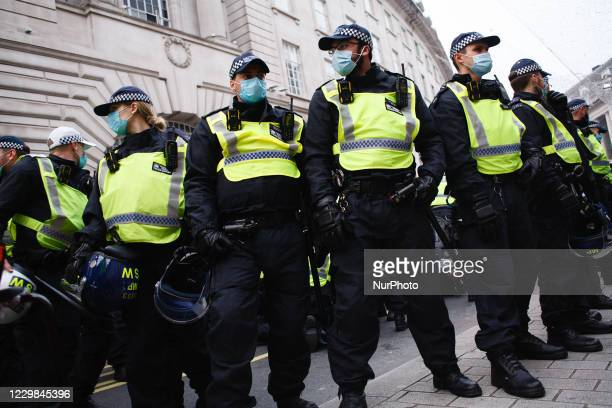 Police officers in riot gear form a cordon amid scuffles with activists on Regent Street during an anti-lockdown demonstration in London, England, on...