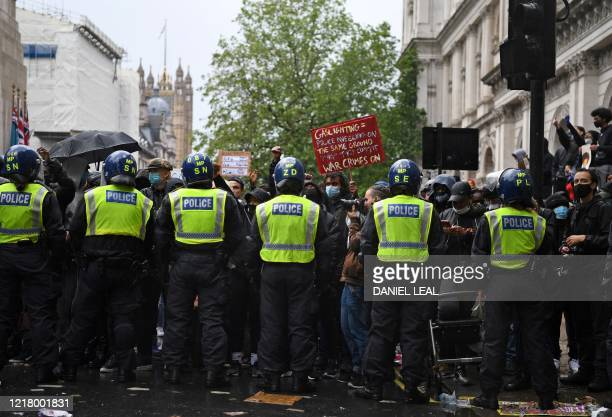 TOPSHOT Police officers in riot gear form a line in front of protestors on Whitehall near to Downing Street in central London on June 6 during a...