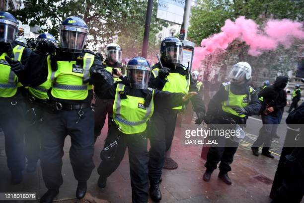 TOPSHOT Police officers in riot gear shout to protestors near Downing Street in central London on June 6 during a demonstration organised to show...