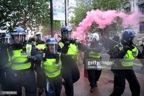 Police officers in riot gear shout to protestors near Downing Street in central London on June 6 during a demonstration organised to show solidarity...
