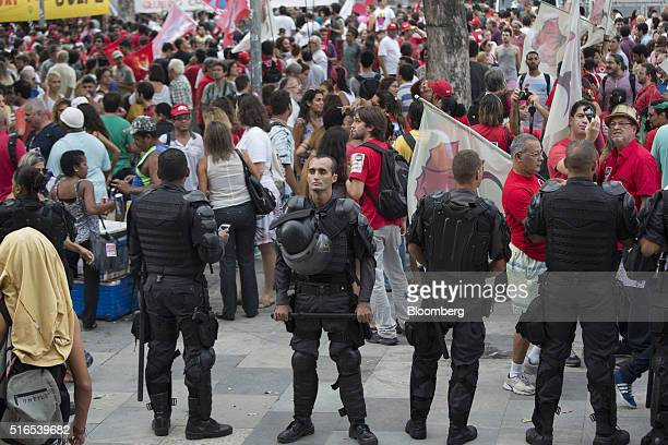 Police officers in riot gear stand guard as demonstrators participate in a protest in favor of Brazil's President Dilma Rousseff in Rio de Janeiro...