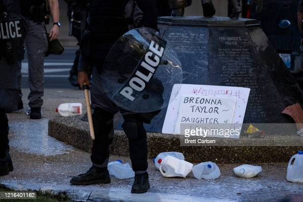 Police officers in riot gear stand in and around the milk jugs broken by two men moments earlier on May 30, 2020 in Louisville, Kentucky. Protests...