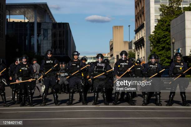 Police officers in riot gear stand in formation at a cross street as they make their way to where protesters are gathered on May 30 2020 in...