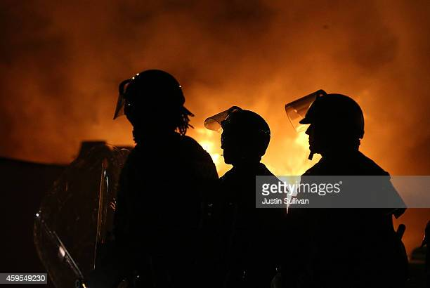 Police officers in riot gear stand in front of a burning building during a protest on November 24 2014 in Ferguson Missouri A St Louis County grand...