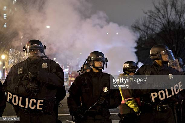 Police officers in riot gear stand near a fire that was extinguished during a demonstration near Franklin Square after the 58th presidential...
