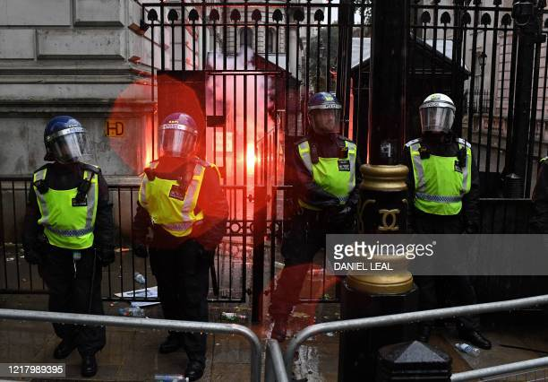 Police officers in riot gear stand on duty as a flare thrown by protesters burns inside Downing Street during an antiracism demonstration in central...