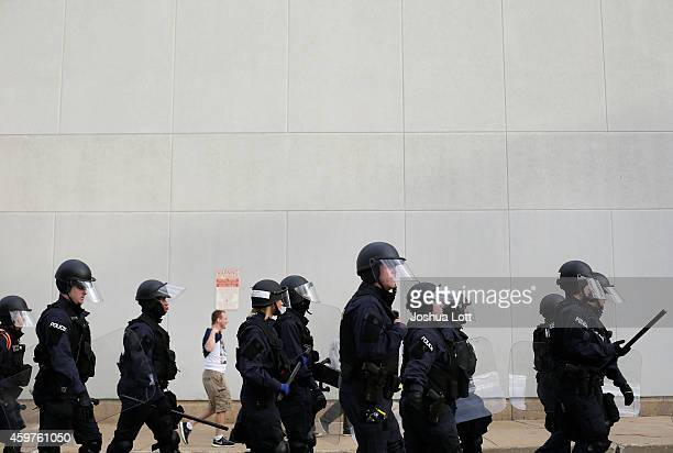 Police officers in riot gear trail demonstrators protest the shooting death of Michael Brown November 30 2014 in St Louis Missouri Brown a 18yearold...