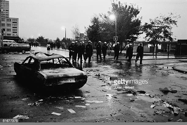 Police officers in riot gear walk past a burnedout car the morning after the riot on the Broadwater Farm housing estate Tottenham London 7th October...