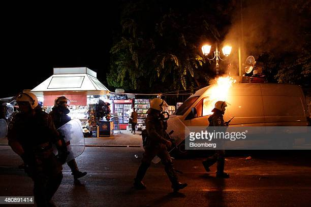 Police officers in riot gear walk past a television broadcast vehicle set on fire by antibailout protestors during a demonstration outside the Greek...