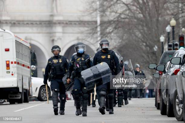 Police officers in riot gear walks towards the U.S. Capitol as protesters enter the building on January 06, 2021 in Washington, DC. Trump supporters...