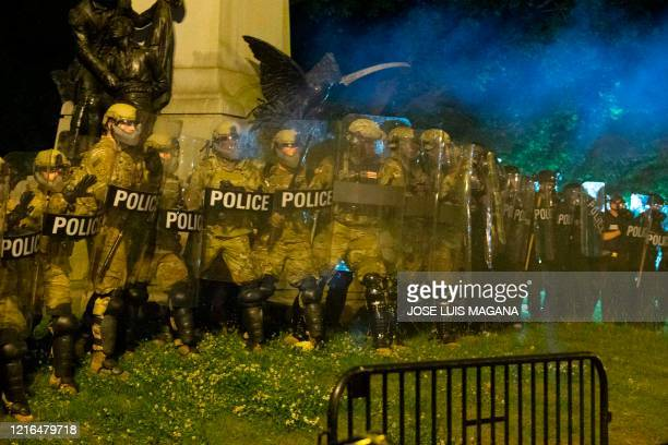 Police officers in riot gear watch demonstrators as they chant outside of the White House on May 30 2020 in Washington DC during a protest over the...