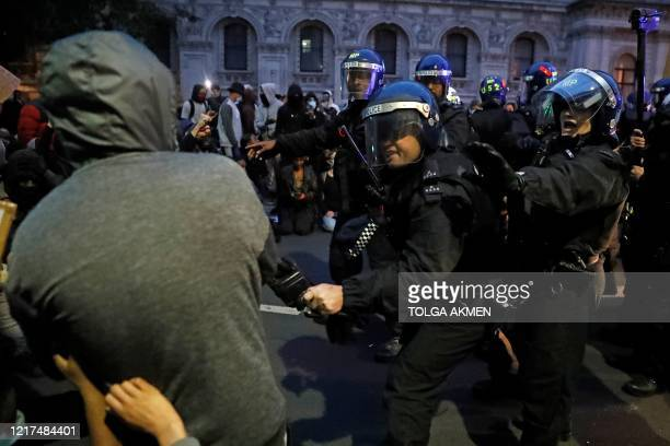 Police officers in riot helmets reacts as protestors attempt to stop a police van leaving during an antiracism demonstration in London on June 3...