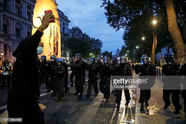 Police officers in riot helmets walk along Whitehall during an antiracism demonstration in London on June 3 after George Floyd an unarmed black man...