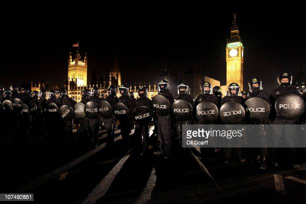 Police officers in riot wear contain student protesters on Westminster Bridge on December 9 2010 in London England Parliament voted today to...