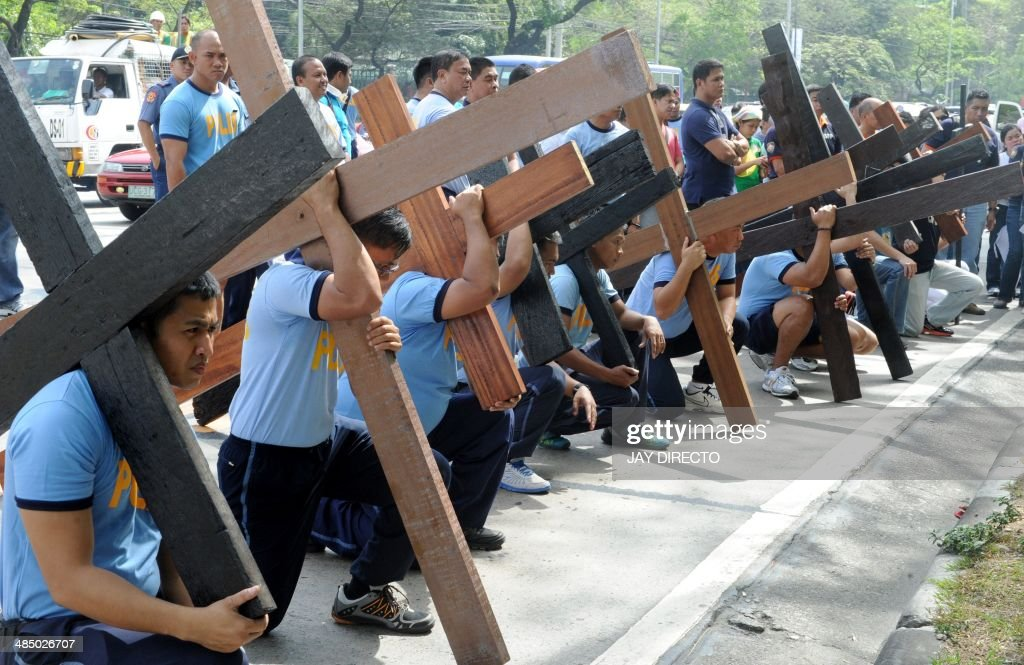 Police officers in the Philippine capital Manila carry wooden crosses on April 16, 2014 to imitate the suffering of Jesus Christ and as a means to atone for their sins. Various acts of penitence, including men carrying heavy crosses or whipping their bare backs bloody with strips of bamboo, and men and women being ceremonially nailed to crosses are a feature of Lent in the Philippines, Asia's Catholic outpost. AFP PHOTO / Jay DIRECTO