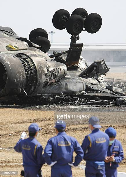 Police officers inspect a buntout FedEx cargo plane after it crashlanded on the runway of the Narita International Airport in Narita city in Chiba...