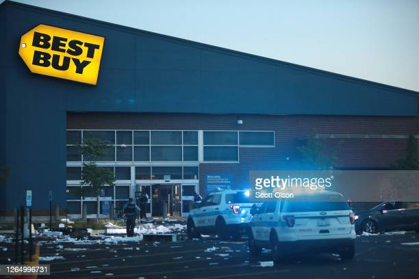 Police officers inspect a damaged Best Buy store after parts of the city had widespread looting and vandalism on August 10 2020 in Chicago Illinois...