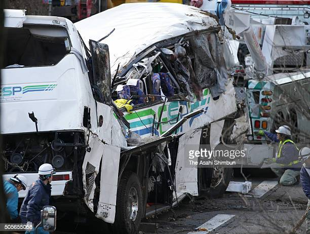 Police officers inspect a night ski bus after the accident killing at least 14 people and injuring 27 on January 15 2016 in Karuizawa Nagano Japan...