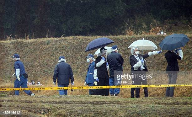 Police officers inspect a site where a man stabbed five people to death at Sumoto city in Awajishima island Hyogo prefecture western Japan on March 9...