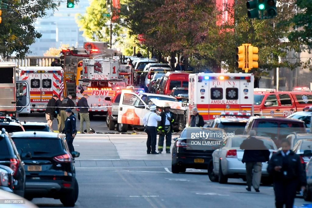 TOPSHOT - Police officers inspect a truck following a shooting incident in New York on October 31, 2017. Several people were killed and numerous others injured in New York on Tuesday when a suspect plowed a vehicle into a bike and pedestrian path in Lower Manhattan, and struck another vehicle on Halloween, police said. A suspect exited the vehicle holding up fake guns, before being shot by police and taken into custody, officers said. The motive was not immediately apparent. PHOTO / Don EMMERT